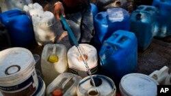 Warga mengisi tong-tong plastik dengan air di sebuah daerah kumuh di New Delhi (23/2). (AP/Bernat Armangue)
