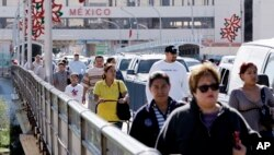 FILE - Pedestrians cross the Gateway to the Americas International Bridge from Mexico into the U.S. in Laredo, Texas, Dec. 3, 2007.