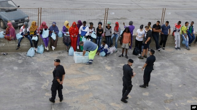 Migrants wait to board a ferry boat from the port of Lampedusa, for Sicily, southern Italy, where they will be sent to other camps based on their legal status, Oct. 7, 2013.