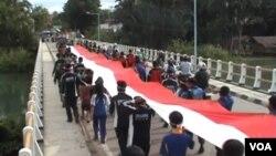 Bendera merah putih sepanjang 100 meter diarak melintasi 27 desa menuju ibukota Poso dalam peringatan Hari Pahlawan (10/11).
