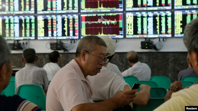 An investor uses his mobile phone in front of electronic screens showing stock information at a brokerage house in Wuhan, Hubei province, August 16, 2013.