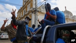 Armed pro-government militia members flash victory signs as they occupy the Monimbo neighborhood of Masaya, Nicaragua, July 18, 2018.