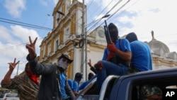 Milicianos progubernamentales armados muestran señales de victoria mientras ocupan el barrio Monimbó en Masaya, Nicaragua, el 18 de julio de 2018.