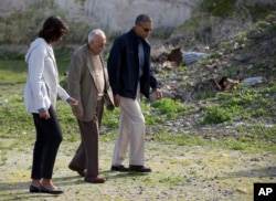 FILE - Then-U.S. President Barack Obama, right, and first lady Michelle Obama, left, tour Robben Island with Ahmed Kathrada, June 30, 2013, in South Africa.