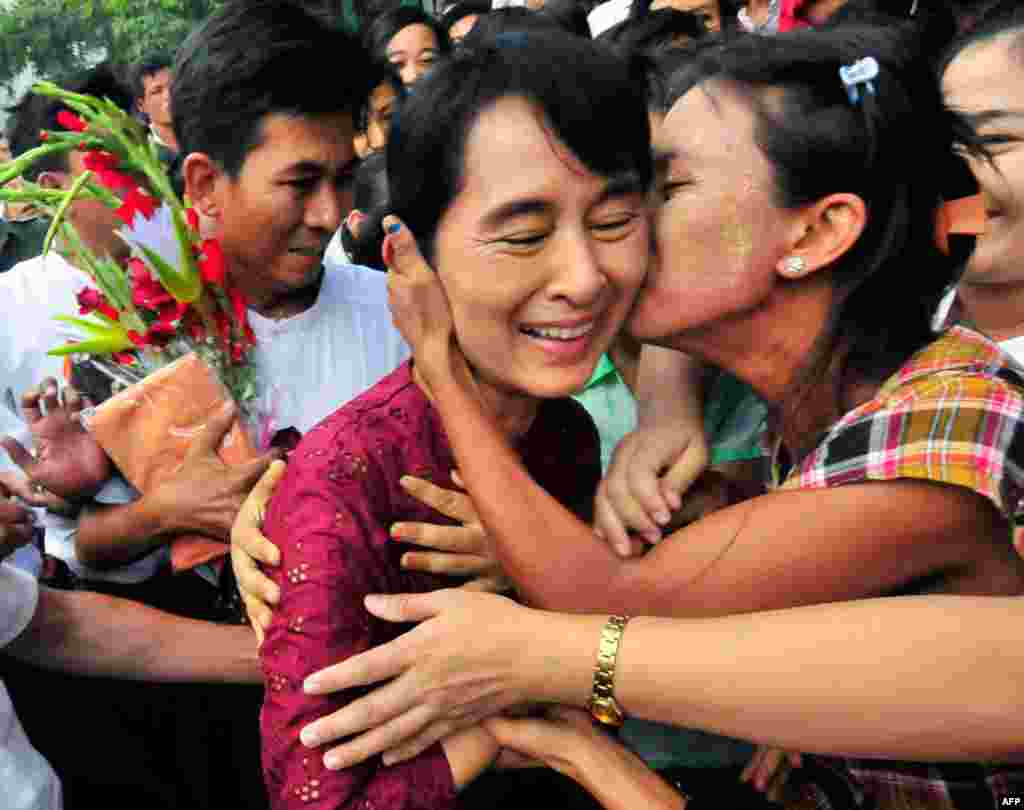 July 7: Myanmar democracy icon Aung San Suu Kyi is greeted as she visits Nyaung Oo market in Myanmar. Suu Kyi was visiting the village with her youngest son Kim Aris and members of the National League for Democracy party. (AP Photo/Khin Maung Win)
