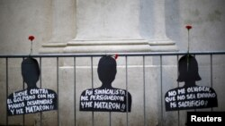 "FILE - Cut-out depicting victims of human rights abuse during the rule of former dictator Augusto Pinochet hang on a fence next to the ""La Moneda"" Presidential Palace during a rally in Santiago, Sept. 11, 2015."