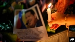 Một phụ nữ đặt một ngọn nến trước bức ảnh của Tổng thống Hugo Chavez bên ngoài Đại sứ quán Venezuela ở La Paz, Bolivia, 5/3/13