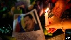 Uma mulher coloca uma vela junto a uma imagem do presidente venezuelano Hugo Chávez