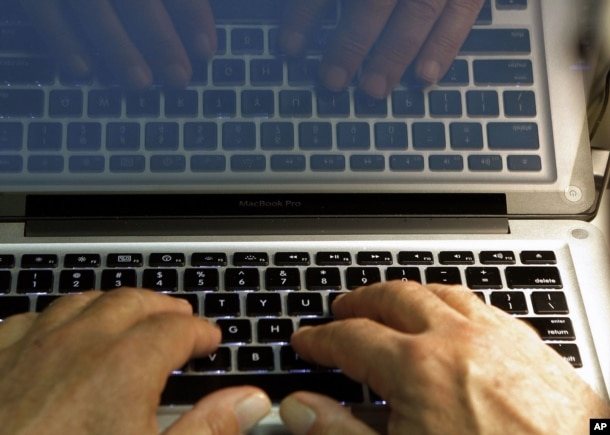 FILE - Hands type on a computer keyboard in Los Angeles, Feb. 27, 2013.