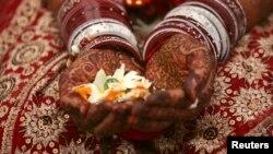 Seorang pengantin perempuan memegang bunga dengan tangannya dihiasi pasta henna selama upacara pernikahannya di kota Ahmedabad, India barat, 22 Januari 2012. (Foto: Reuters)