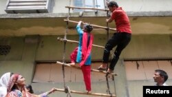 Garment workers from textile company Envoy Group demonstrate climbing a makeshift ladder, which serves as a fire exit to the building, during a protest in Dhaka, June 10, 2013.