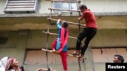 Công nhân của công ty may mặc Envoy Group thao diễn về cách chiếc leo thang tạm được dùng như một cách thoát khi có hỏa hoạn trong một cuộc biểu tình phản đối ở Dhaka 10/6/13