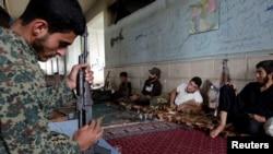 2016年5月17日,什叶派的反抗组织的一名战士在叙利亚南部的一个村庄擦拭武器,准备战斗。