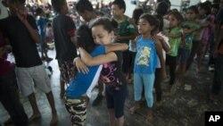 Niñas hondureñas se abrazan mientras esperan en la fila la oportunidad de jugar en el patio de recreo en un campamento establecido por una caravana de miles de migrantes centroamericanos en Juchitán, México, 31 de octubre de 2018.