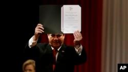 El presidente de Paraguay, Horacio Cartes, muestra el certificado que lo declara senador electo, durante una ceremonia en Asunción, Paraguay, el viernes 25 de mayo de 2018.