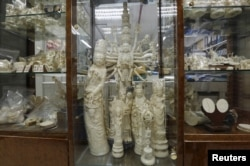 FILE - Products from elephant ivory are displayed on the centre column of a shelf inside a carving and jewellery factory in Hong Kong, Oct. 23, 2015.