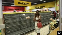 A woman walks past almost empty bread shelves in a shop in Harare, Tuesday, Oct, 9, 2018.