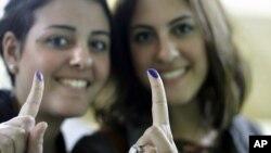 11月28日在开罗,埃及妇女投票后向人们显示她们蘸了油墨的手指