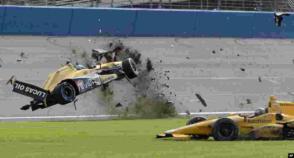 ឡានប្រណាំងរបស់លោក Ryan Briscoe (ឆ្វេង) បានប៉ើងចូលវាលស្មៅនៅក្នុងការប្រកួតប្រណាំងឡាន IndyCar នៅក្នុងឯ Auto Club Speedway ក្នុងទីក្រុង Fontana រដ្ឋកាលីហ្វញ៉ា សហរដ្ឋអាមេរិក កាលពីថ្ងៃទី២៧ ខែមិថុនា ឆ្នាំ២០១៥។