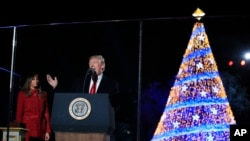 President Donald Trump speaks as first lady Melania Trump listens during the lighting ceremony for the 2017 National Christmas Tree on the Ellipse near the White House in Washington, Nov. 30, 2017.