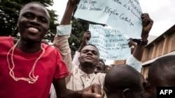 Des manifestants brandissent des pancartes lors d'une marche Kinshasa le 12 janvier 2018.