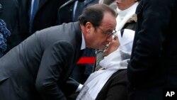 Le président français François Hollande embrasse la mère du défunt policier Ahmed Merabet cours des commémorations à Paris, mardi 5 janvier 2016.