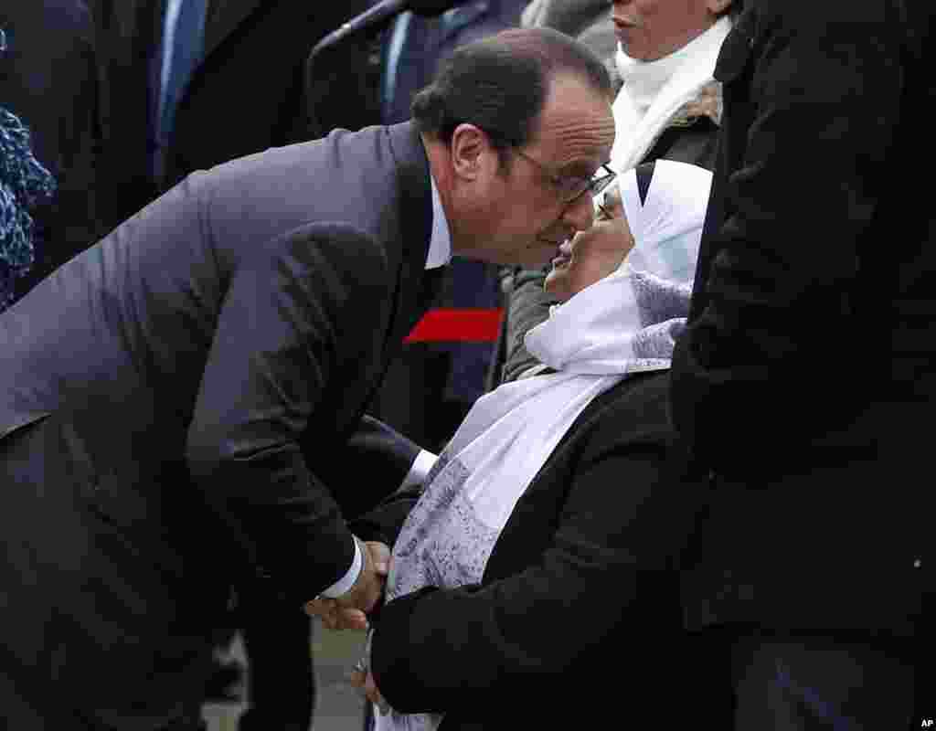 French President Francois Hollande kisses late police officer Ahmed Merabet's mother during commemorations in Paris, Tuesday Jan. 5, 2016.