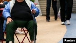 FILE - An overweight woman sits on a chair in Times Square in New York, May 8, 2012.