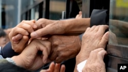 FILE - South Koreans and their North Korean relatives on a bus grip hands to bid farewell after the Separated Family Reunion Meeting at Diamond Mountain resort in North Korea, Oct. 22, 2015. Hundreds of elderly Koreans wept and embraced as they parted — perhaps for good — after briefly reuniting for the first time in more than 60 years.