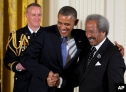 FILE- President Barack Obama welcomes Allen Toussaint to award him the 2012 National Medal of Arts for his contributions as a composer, producer, and performer, during a ceremony in the East Room of White House in Washington, July 10, 2013.