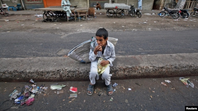 "A child sits along a road median as he eats his breakfast of a single piece of ""roti"" (South Asian bread) while waiting for work in Karachi early morning May 6, 2012."