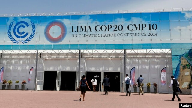 People walk at the venue of the U.N. Climate Change Conference COP 20 in Lima, Peru, Dec. 4, 2014.
