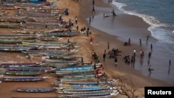 FILE - People are pictured on a beach next to fishing canoes in Dakar, Senegal, June 21, 2013.