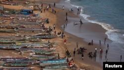 Photo d'archives : des gens sont photographiés sur une plage à côté de pirogues de pêche à Dakar, au Sénégal, le 21 juin 2013.