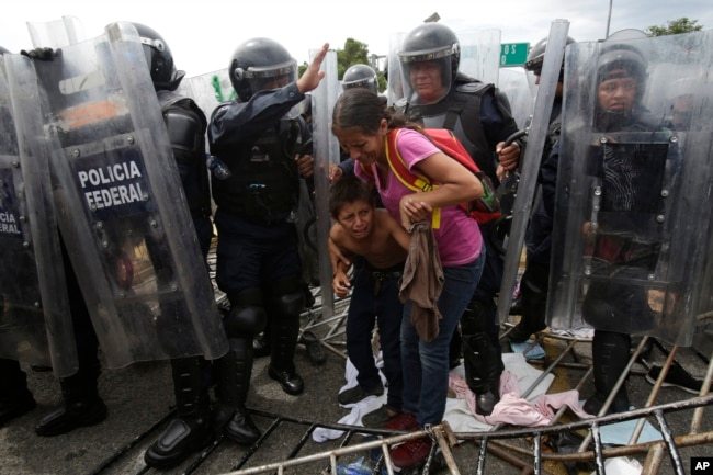 A Honduran migrant mother and child cower as they are surrounded by Mexican Federal Police in riot gear, at the border crossing in Ciudad Hidalgo, Mexico, Oct. 19, 2018.