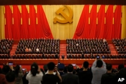 FILE - Journalists take pictures of Chinese President Xi Jinping, front row center, and other Communist Party officials at Party Congress at the Great Hall of the People in Beijing, Oct. 24, 2017. Journalists in China are educated to serve the party, says a journalism professor of at China's Guangzhou University.
