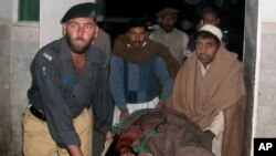 People carry an injured member of police station staff in Daraban near Dera Ismail Khan, Pakistan, November 23, 2011.