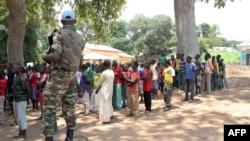 Un soldat monte la garde près d'anciens enfants soldats anti-Balaka attendant d'être libérés d'un camp à Batangafo, en République centrafricaine, 28 août 2015.