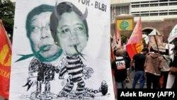Para pengunjuk rasa menampilkan spanduk yang memperlihatkan Sjamsul Nursalim (kiri) dan Anthony Salim (kanan) - dua orang terkaya di Indonesia yang dituduh menggelapkan jutaan dolar melalui BLBI pada 1998, Jakarta, 22 Juli 2008. (Foto: AFP/Adek Berry)
