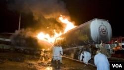 Tim pemadam kebakaran Pakistan mencoba memadamkan kebakaran sebuah truk tangki minyak setelah serangan oleh Taliban.