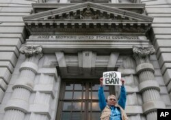 FILE - Karen Shore holds up a sign outside of the 9th U.S. Circuit Court of Appeals in San Francisco, Feb. 7, 2017.
