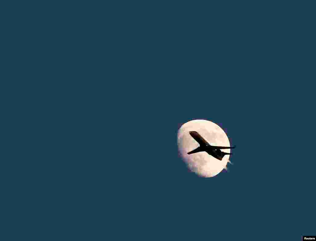 An airplane is seen agains the moon in its waxing gibbous phase in the sky over Hoboken, New Jersey, USA, June 19, 2013. On Sunday, June 23, a perigee moon will coincide with a full moon when it will pass by the earth at its closest point.