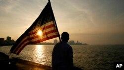 Un estudiante mexico-estadounidense que estudia en Cuba observa el atardecer en el Malecón de La Habana, ondeando una bandera de Estados Unidos.