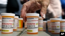 FILE -Family and friends who have lost loved ones to OxyContin and opioid overdoses leave pill bottles in protest outside the headquarters of Purdue Pharma, which is owned by the Sackler family, in Stamford, Conn., Aug. 17, 2018.
