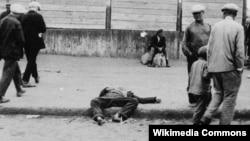 Xarkovda sakinlər acından ölmüş adamın cəsədinin yanı ilə keçirlər. 1932.