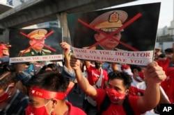 Warga Burma yang tinggal di Thailand memegang foto Panglima Tertinggi militer Myanmar Jenderal Min Aung Hlaing saat melakukan protes di depan Kedutaan Besar Myanmar, di Bangkok, Thailand, Senin, 1 Februari 2021. (Foto: AP)