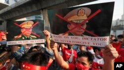 Burmese living in Thailand hold pictures of Myanmar military Commander-in-Chief Senior Gen. Min Aung Hlaing during a protest in front of the Myanmar Embassy, in Bangkok, Thailand, Monday, Feb. 1, 2021.