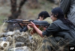 FILE - A member of the Free Life Party, or PJAK, trains on a weapon at the group's camp in the Qandil mountains in northern Iraq.