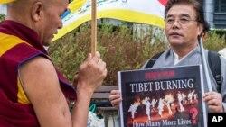 """Đại biểu Quốc hội Tây Tạng lưu vong, ông Thubten Wangchen (trái) thực hiện cuộc biểu tình có tên """"Ngọn lửa của Chân lý"""" gần trụ sở Ủy hội châu Âu ở Brussels,"""