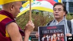 """Đại biểu Quốc hội Tây Tạng lưu vong Thubten Wangchen (trái) thực hiện cuộc biểu tình có tên """"Ngọn lửa của Chân lý"""" gần trụ sở Ủy hội châu Âu ở Brussels"""